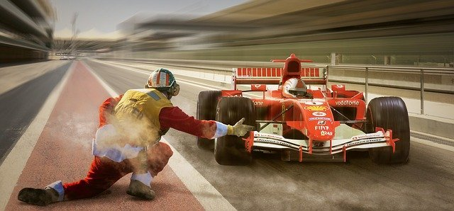 Formula one Ferrari racing car getting a go from a men