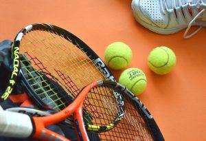 tennis racket 3 tennis balls and a white shoe