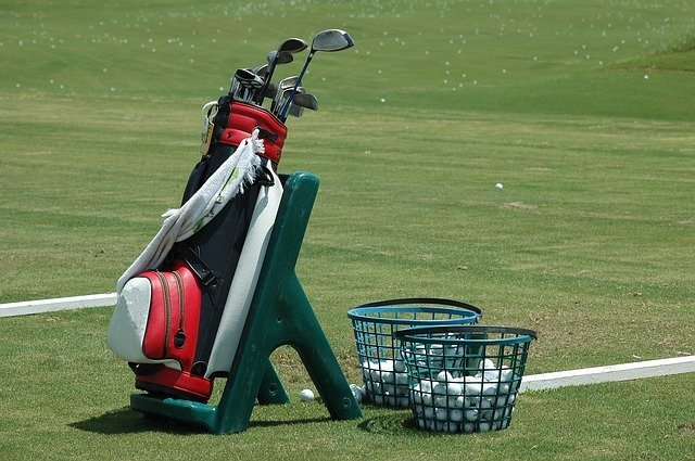 golf bag with two golf basket with balls inside on a golf court