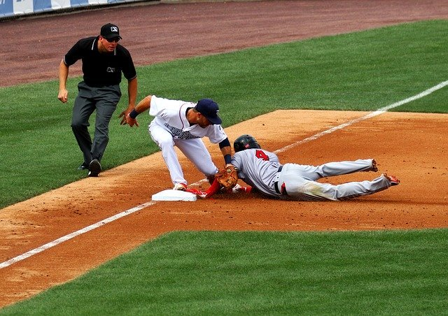 2 baseball players tag out on third base with a referee looking at them